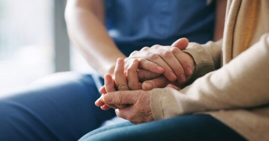 A man holding an older person's hand.