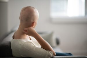 A woman is indoors in her living room. Her head is shaved due to chemotherapy. She is sitting and looking thoughtful.