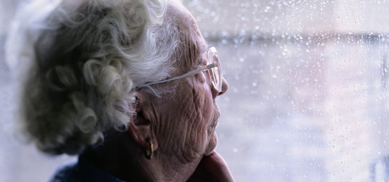 Elderly woman looking out of window