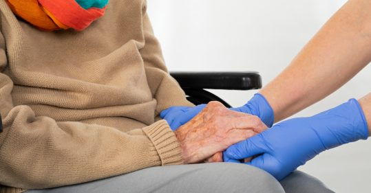 Healthcare professional holding patient's hand