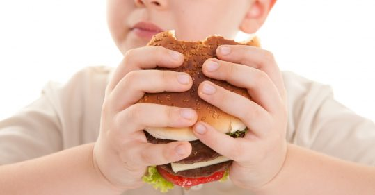 Child eating burger.